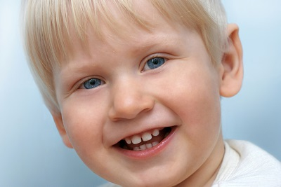 young blonde boy smiling with first teeth